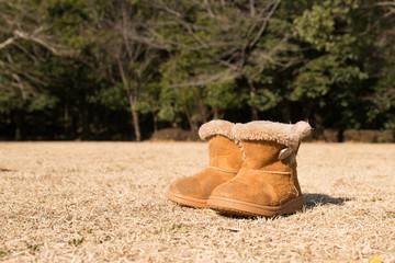 冬の芝生に置かれた子供用のブーツ