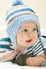 Cute baby boy wearing of warm knitted hat and gloves