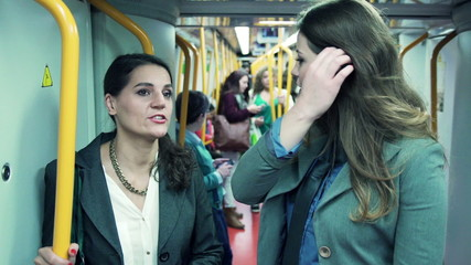 Two happy businesswomen talking during metro ride