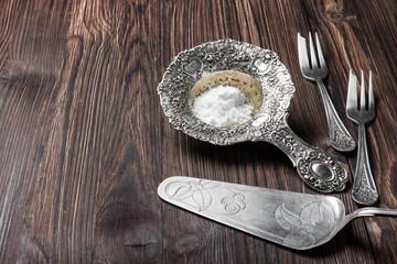 silver cutlery for dessert on a dark wooden background
