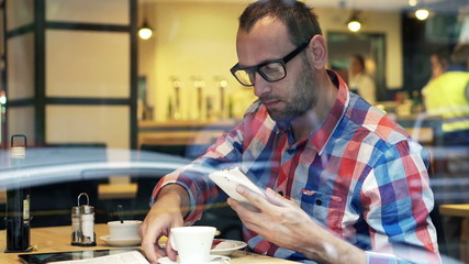 Trendy man talking photo with cellphone sitting in cafe
