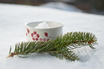 Winter mug in snow with pine