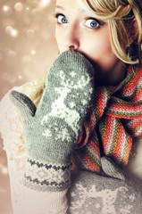 Surprised woman wearing reindeer mittens.