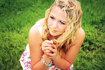 Young woman smelling a small flower.
