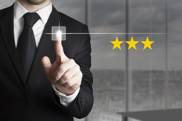 businessman pushing button three stars