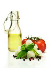 Oil , tomatoes, mozzarella and basil isolated on white