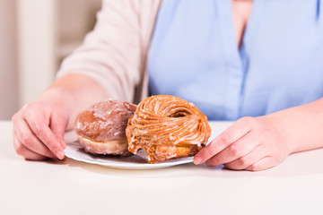 Woman pointing with her hands a plate of sweet donuts in the kit