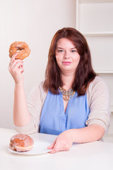 Plump woman holding a donut in her hand at the table