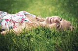 Fototapety Smiling woman lying in the grass.