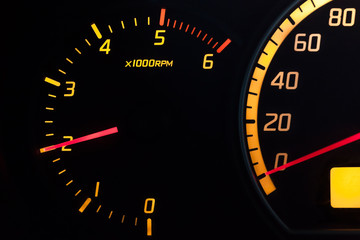 Tachometer with yellow backlit glowing dial and red needle.