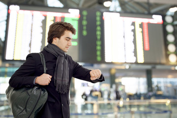 Youngman looking at watch at airport