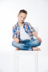 Junge sitzt lässig auf einem Stuhl