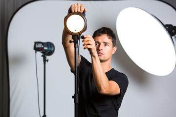 Young pro photographer in his studio setting up lights