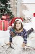 Beautiful young woman in Santa hat lying on floor near Chr