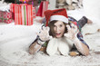 Beautiful young woman in a Santa hat lying on the floor near Chr