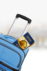 Sweden. Blue suitcase with guidebook.