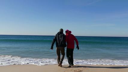 Happy Middle-aged Couple Walking on Ocean Sandy Beach