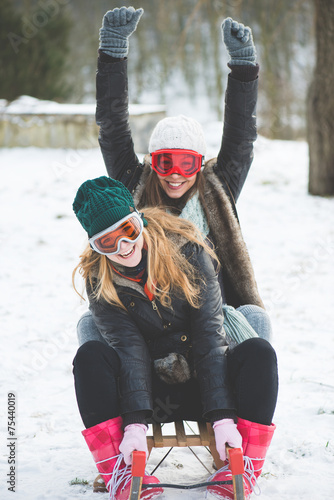 canvas print picture Laughing girls sledge downhill in wintertime enjoy snow