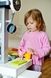 toddler girl playing toy kitchen