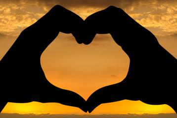silhouettes de mains forme coeur, coucher de soleil