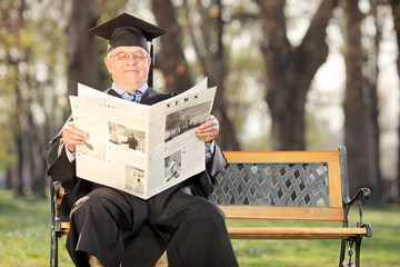 Mature college professor reading the news in park