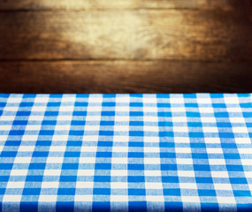 Checkered blue tablecloth over wooden background