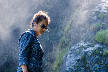 Young Nepalese woman standing next to a waterfall