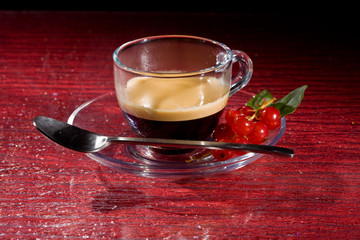 Espresso coffee with currants on red glasstable