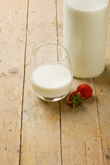 Milk on wooden table with strawberry
