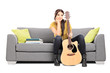 Beautiful female guitarist sitting on a sofa