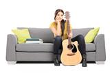 Beautiful female guitarist sitting on a sofa