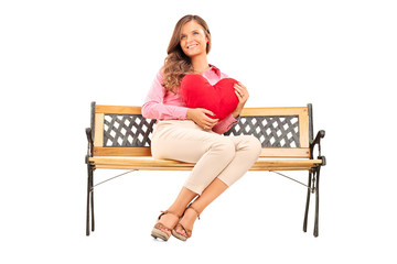 Beautiful girl holding a red heart seated on bench
