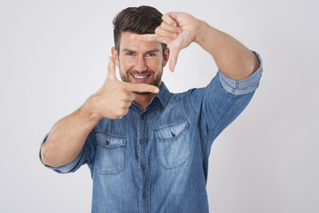 Studio shot of handsome man framing his face