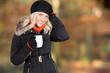 Junge blonde Frau mit Mütze und Tasse in der Hand