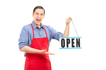 Young retail worker holding an open sign