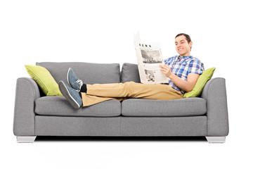 Young happy man reading the news on a sofa