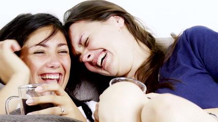 Two beautiful women having fun laughing watching tv closeup