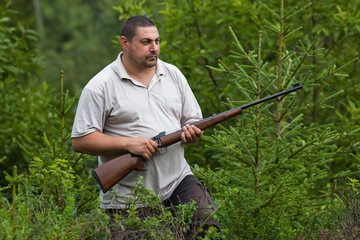 the hunter with rifle in a forest