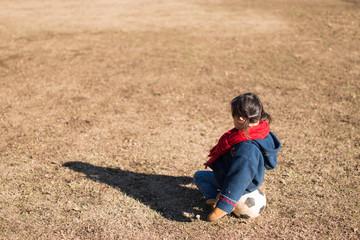 サッカーボールに座る少女