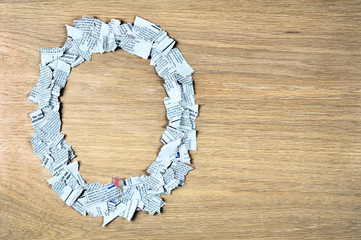 Round frame made of shredded newspaper pieces.