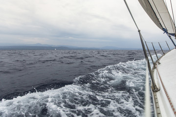 Sailing yacht on the race in a stormy sea. Luxury yachts.