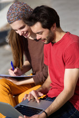 Couple students working on laptop together outdoors