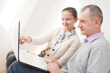 Girl teaching to use a laptop by senior man
