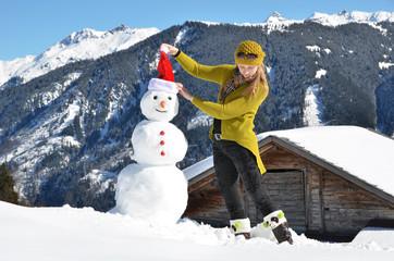 Girl decorating a snowman