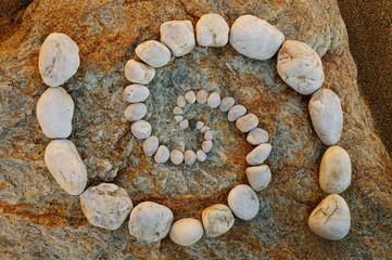Esoterische Doppelspirale aus Kieselsteinen