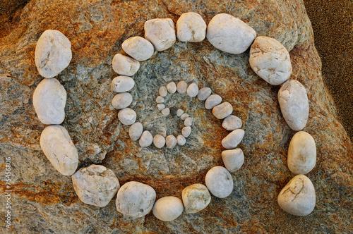 Foto op Canvas Spiraal Esoterische Doppelspirale aus Kieselsteinen
