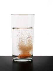 Vitamin tablet dissolving in glass of water. Fizzing.