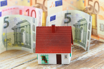 House with banknotes in the background