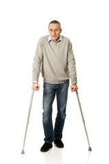 Full length mature man with crutches