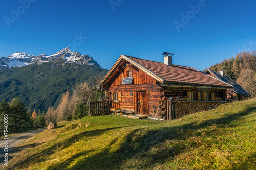 old wooden hut cabin in mountain alps at rural fall landscape - 75460058